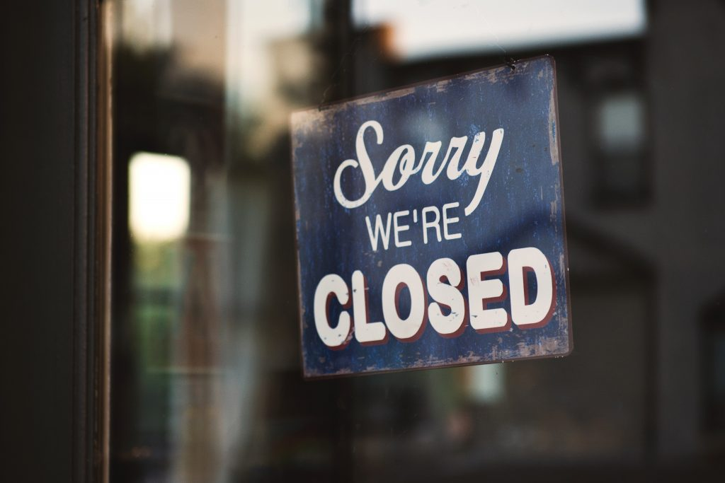 Sorry we are closed sign hanging on business door.
